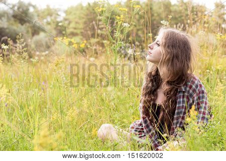 Beautiful young woman with long curly brown hair dressed in a check shirt is sitting on a meadow in high grass and gentle wild flowers