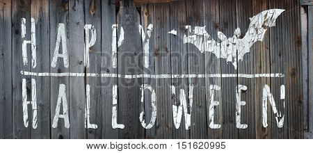 Happy Halloween banner. Greeting lettering on the old fence. Horizontal banner with a bat. Cracked paint and old fence texture. Realistic 3d illustration. Design template. Modern style.