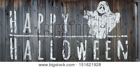Happy Halloween banner. Greeting lettering on the old fence. Horizontal banner with a very cute funny ghost. Cracked paint and old fence texture. Realistic 3d illustration. Design template. Modern style.