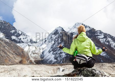 Woman Hiker Meditating on Rocks in Himalaya Mountains Nepal. Young Girl Looking at Beautiful Inspirational Landscape. Recreation Meditating Outdoors in High Mountains in Nepal.