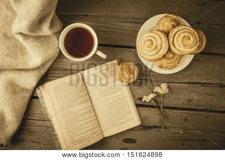 Cozy breakfast in spring or early autumn tea, freshly baked scones and bouquet of field's daisy and fascinating book. Toned