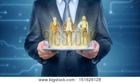Someone holding a tablet that is showing a hologram of two men and a woman wearing office clothing. High technology and electronics. Driving business innovation. Digital data management.