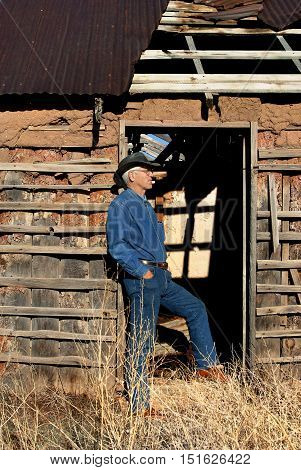 Man leans against dilapidated doorway of an old adobe in New Mexico. Roof is collapsing and adobe clay is crumbling.