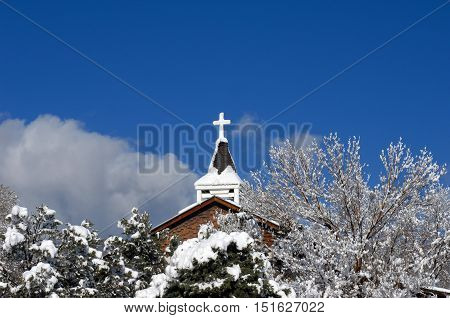 Catholic Mission is covered by a fresh covering of snow. Church steeple is framed by vivid blue sky.