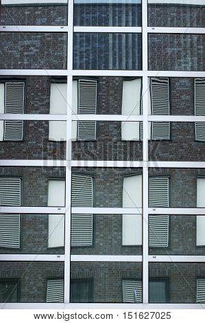 The abstract reflection of windows with window shutters in mirror windows.