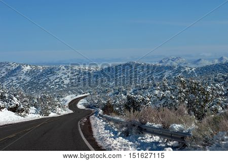 S shaped curving road disappears into the mountaijns of central New Mexico. Snow covers mountains and trees. Blue sky.