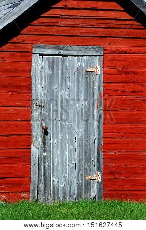 Rustic wooden door sits on front of an old red smokehouse in rural Wisconsin. Hook holds door closed.