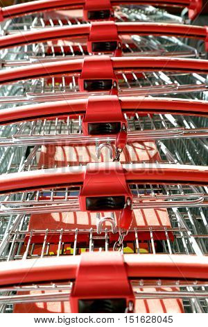 Row of parked shopping carts with red handle..