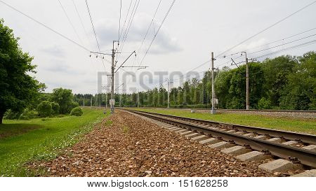 Electric-railway tracks in a suburban rural scene
