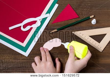 Creating a Christmas decoration for table setting. Decor for serviette in form of Santa Claus. Children project step by step photo instructions. Step 4. The child glues the parts of Santa Claus
