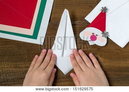 Creating a Christmas decoration for table setting. Decor for serviette in form of Santa Claus. Children project step by step photo instructions. Step 7. Child folded napkin