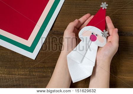 Creating a Christmas decoration for table setting. Decor for serviette in form of Santa Claus. Children project step by step photo instructions. Step 9. Final design for serviette in hands of child