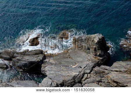 Rocky sea shore in Manarola in Liguria Italy. One of five Cinque Terre cities (unesco world heritage)