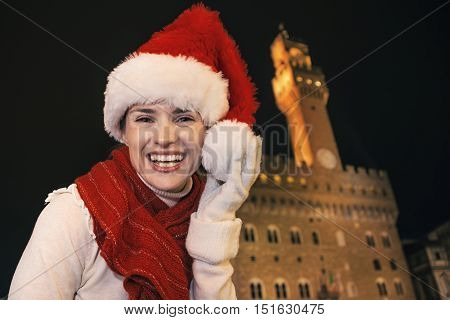 Trip full of inspiration at Christmas time in Florence. Portrait of happy modern tourist woman in Christmas hat in the front of Palazzo Vecchio in Florence Italy having fun time