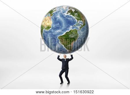Businessmen holding the Earth up above himself on a white background. World domination. Running the planet. Business advantage. Conquering the market. Elements of this image are furnished by NASA.