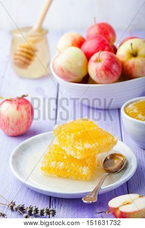 Honey, honeycombs and fresh apples on a lavender wooden background