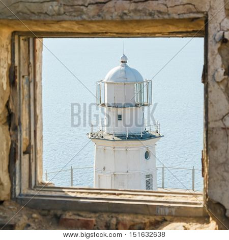 white lighthouse on the background of the sea in window of destroyed building