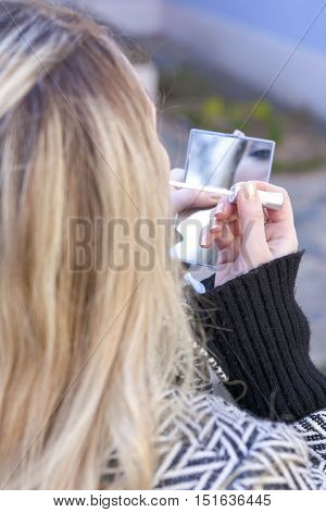 Young Caucasian Blond Female Applying Lips Make Up On The Move Outdoors. Vertical Image Orientation