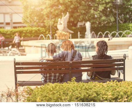 Couple sitting on the bench in the park a sunny day