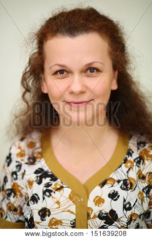 Portrait of smiling curly woman looking at camera in home robe