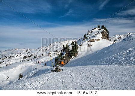 Ski route in Austrian Alps. Skiers skiing down the mountain ski slopes