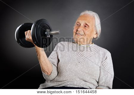 Happy Senior Woman Doing Exercise With Dumbbell Over Grey Background