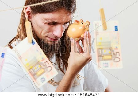 Savings concept. Young handsome long haired thinking man holding piggybank moneybox around banknotes cash.