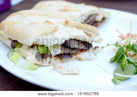 Steak baguette with coleslaw and watercress served on a white plate