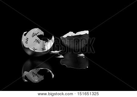 cracked egg shell with countdown on black background, monochrome