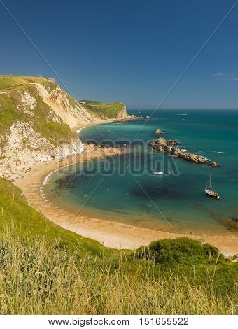 Jurassic coastline with bright blue green sea deep blue skies and yellow sands and cliffs around the Lulworth Durdle Door Worbarrow beaches and coves