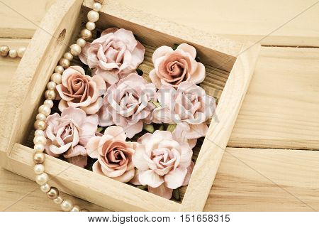 Vintage pink rose and Pearl Necklace on wooden background. Love concept.