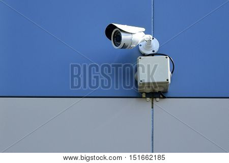 Outdoor surveillance camera on a colored wall.