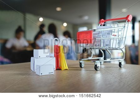 Shopping cart with boxes on desk table .Internet online shopping concept.Vintage tone retro filter effectsoft focus(selective focus)