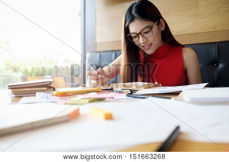 Smiling female student working in a library
