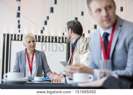 Confident businesswoman talking to businessman in convention center