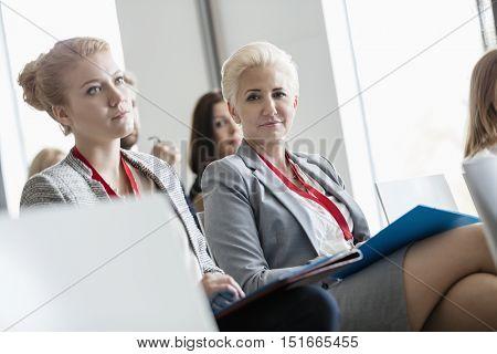 Portrait of confident businesswoman sitting in seminar hall