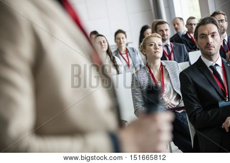Businessman looking at public speaker in convention center