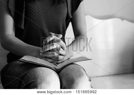 Vintage tone of woman hands on bible. she is reading and praying over bible
