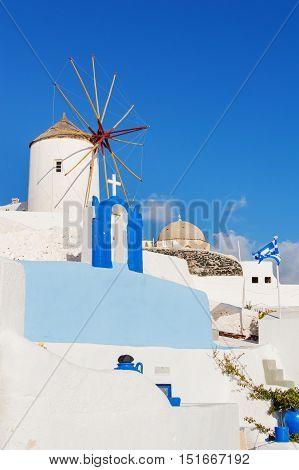 Typical white windmill on street of Oia village Santorini island Greece