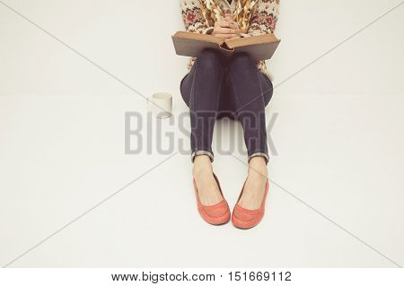 vintage tone of A young woman at home holds an open Bible in her lap