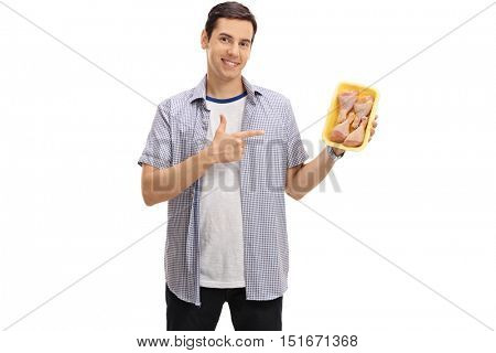 Happy young man holding a pack of chicken drums and pointing isolated on white background
