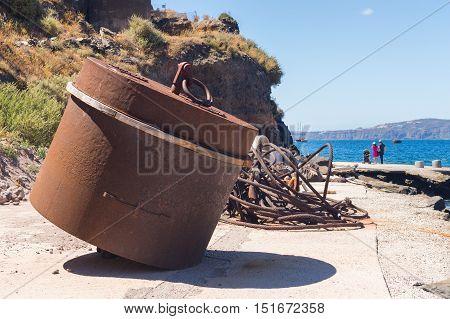 Huge rusty buoy on the sea pier on Santorini island Greece