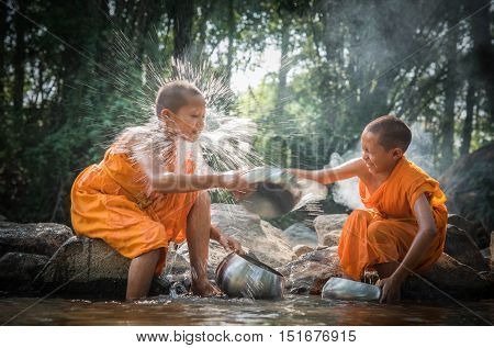 Buddhist Novices Are Cleaning Bowls And Splashing Water In The Summer At The Creek. (songkran Festiv