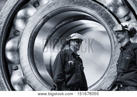 two industry workers inside a giant ball-bearing