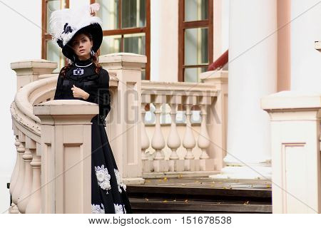 woman in vintage dress on porch of castle