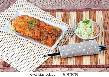 Deep fried dolly fish (Crispy) in Japanese style topped yellow curry with side dish as sliced cabbage and pickled ginger are very delicious