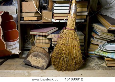 Broom in the foreground and home related objects in mess in the background indoors cropped shot