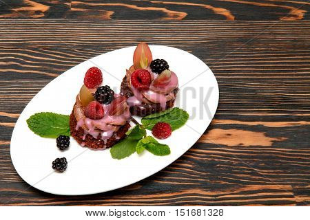 Beautiful chocolate cake with chocolate cream and fresh berries, drizzled with fruit sauce