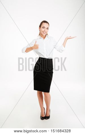 Full length portrait of a young beautiful businesswoman holding copy space on palm and showing thumbs up gesture isolated on white background