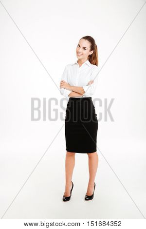 Full length portrait of a smiling businesswoman standing with arms folded isolated on a white background